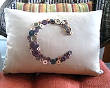 Pillow with monogram made of buttons