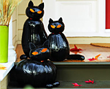 Cat sculptures made from stacked and painted pumpkins