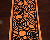 Felt table runner cut to resemble a spider web